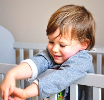 Boy Standing in Cot